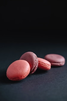 Rosa macarones auf dunklem hintergrund