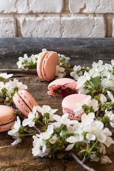 Rosa macarons mit schokoladenganache, karamell und himbeere. blühender zweig französisches delikates dessert. himbeer-makkaroni hochzeits-dessert frühling.