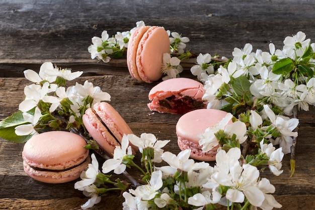 Rosa macarons mit schokoladenganache, karamell und himbeere. blühender zweig