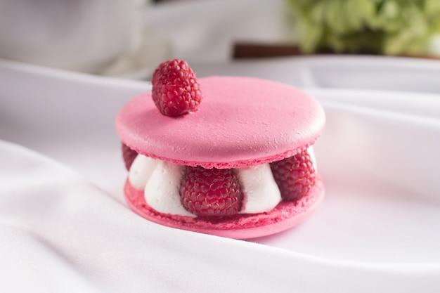 Rosa macarons mit vanillecreme, frische himbeeren