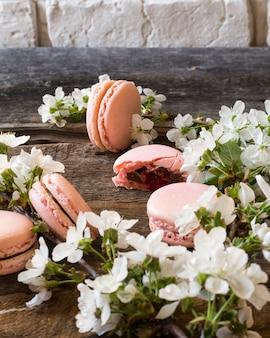 Rosa macarons, schokoladenganache, karamell und himbeere. blühender zweig
