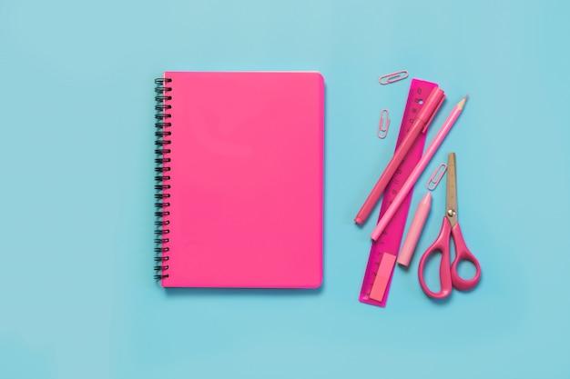 Rosa mädchenhafte schulsachen, notizbücher und stifte auf druckvollem blau. draufsicht, flach liegen.