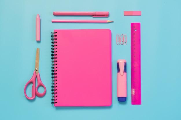 Rosa mädchenhafter schulbedarf, notizbücher und stifte auf schlagkräftigem blau. draufsicht, flach zu legen. kopieren sie platz.
