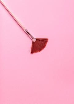 Rosa make-up-pinsel auf rosa hintergrund.