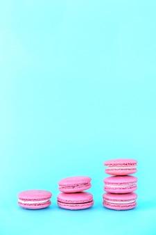 Rosa makronen auf einem blauen hintergrund.