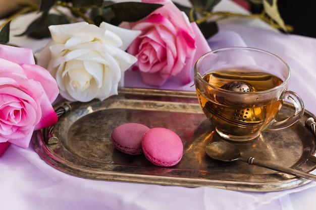 Rosa makronen, heißer tee auf silbernem weinlesebehälter verwischten rosenhintergrund