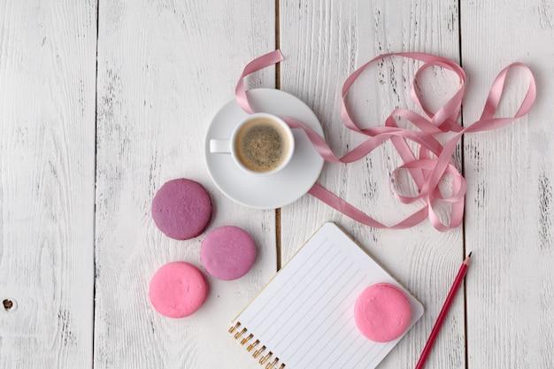 Rosa makronen mit kaffeetasse auf holztisch. flach liegen