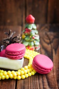 Rosa makronen mit weihnachtsdekorationen auf hölzernem hintergrund