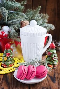 Rosa makronen mit weihnachtsdekorationen und weißer schale auf hölzernem hintergrund