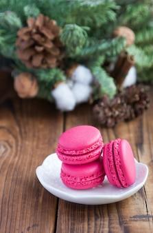 Rosa makronen mit weihnachtsdekorationen woooden an hintergrund