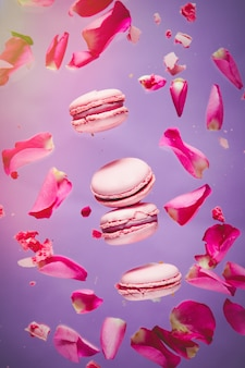 Rosa makronen und rosenblätter fliegen in der luft auf lila wand