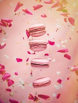 Rosa makronen und rosenblätter fliegen in der luft. ecksonnenlicht