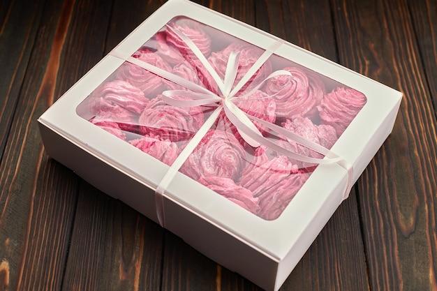 Rosa marshmallow, verpackt in einer schachtel mit einem band, als geschenk, auf einem holzbrett