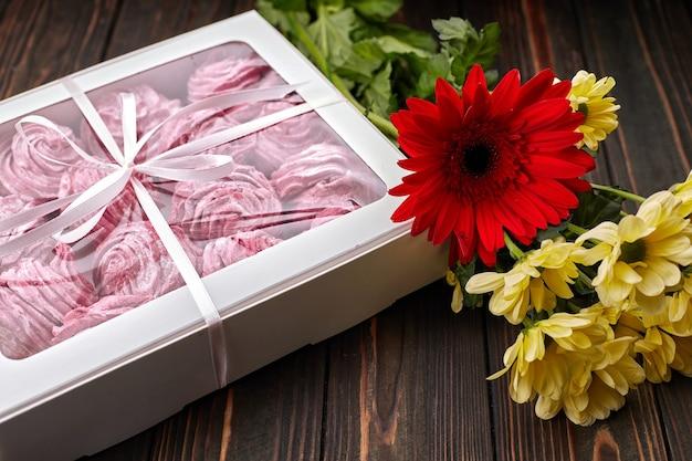 Rosa marshmallow, verpackt in einer schachtel mit einem band und blumen, als geschenk auf einem holzbrett