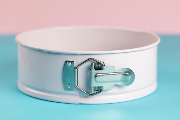 Rosa metallrücken-kuchenring auf blauer und rosa oberfläche
