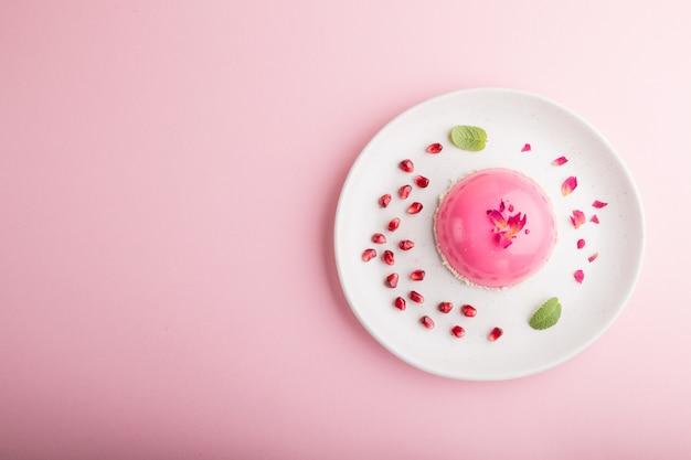 Rosa moussekuchen mit erdbeere auf einem pastellrosa hintergrund. draufsicht, kopierraum.