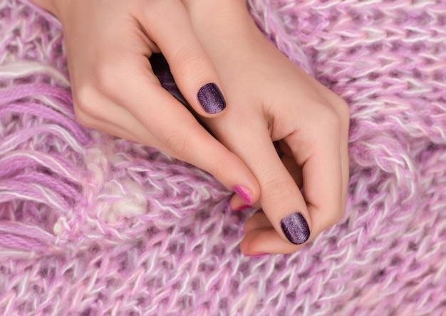 Rosa nageldesign. gepflegte weibliche hände auf rosa hintergrund.