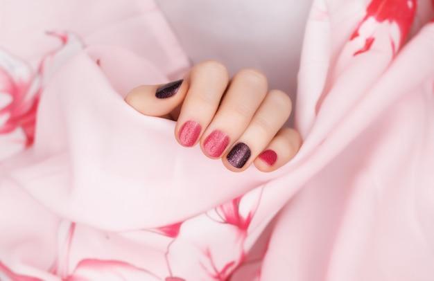 Rosa nageldesign. weibliche hände mit glitzer-maniküre.