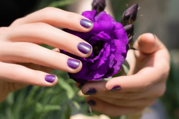 Rosa nageldesign. weibliche hand mit rosa maniküre, die eustoma-blume hält