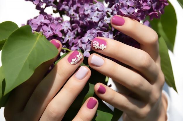 Rosa nageldesign. weibliche hand mit rosa maniküre, die lila flieder hält.