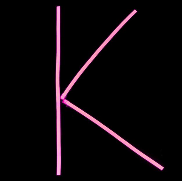 Rosa neonlichter des alphabetes auf schwarzem hintergrund