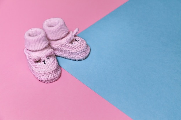 Rosa neugeborene gestrickte schuhe auf einem pastellpapierhintergrund mit kopienraum