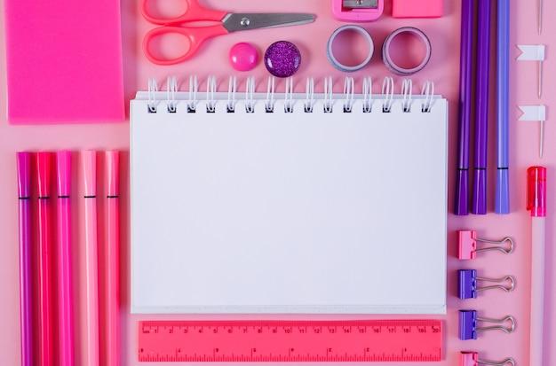 Rosa notizblockstift und marker auf rosa hintergrund flache lage