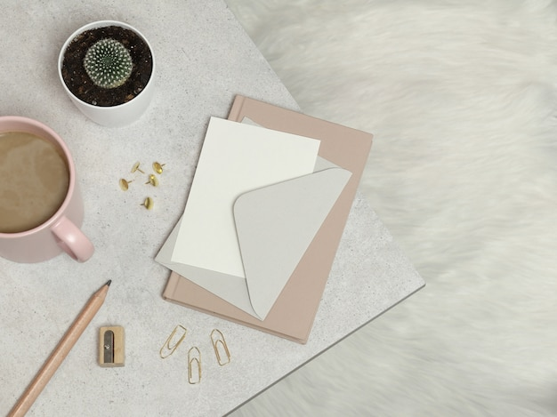 Rosa notizbuch, silberner umschlag, bleistift, bleistiftspitzer, büroklammern, tasse kaffee, kaktus auf granittabelle