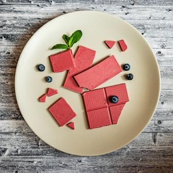 Rosa oder rubinrote schokolade, trendiges dessert auf einem grauen teller auf holztisch