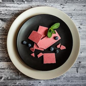 Rosa oder rubinrote schokolade, trendiges dessert auf einem schwarzen teller auf holztisch