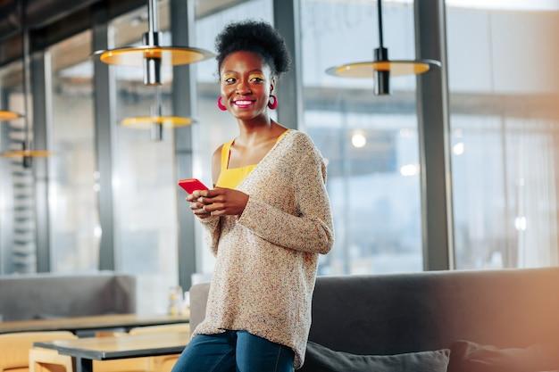 Rosa ohrringe afroamerikanische frau mit hellen lippen trägt rosa ohrringe, die in der nähe des sofas stehen