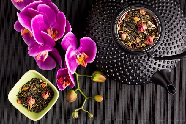 Rosa orchideenblume und trockenes teekraut mit keramischer teekanne der beschaffenheit auf schwarzem tischset