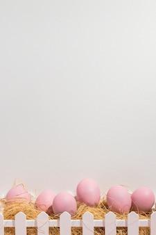 Rosa ostereier auf heu im kasten