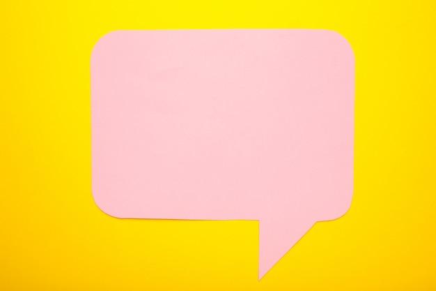 Rosa papier-sprachblasen auf gelbem hintergrund
