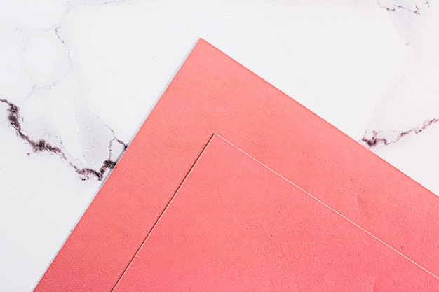 Rosa papiere auf weißem marmorhintergrund als büromaterial flatlay luxus-branding flach und b...