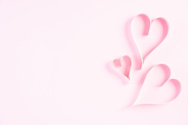 Rosa papierherzen auf rosa papierhintergrund-, liebes- und valentinstagkonzept.