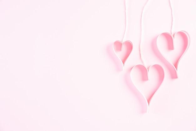 Rosa papierherzen, die an den seilen hängen. liebes- und valentinstagkonzept.