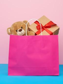 Rosa papiertüte mit einem geschenk und einem teddybär, konzept des einkaufens