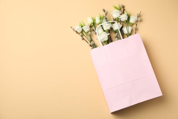 Rosa papiertüte mit rosen und weidenkätzchen auf beigem hintergrund