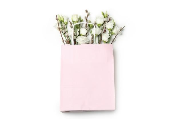 Rosa papiertüte mit rosen und weidenkätzchen lokalisiert auf weißem hintergrund