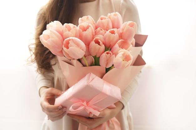 Rosa pastellfarbene tulpen in der frauenhand. junge schöne frau, die einen frühlingsblumenstrauß hält. bündel frisch geschnittener frühlingsblumen in weiblichen händen und rosa geschenkbox.