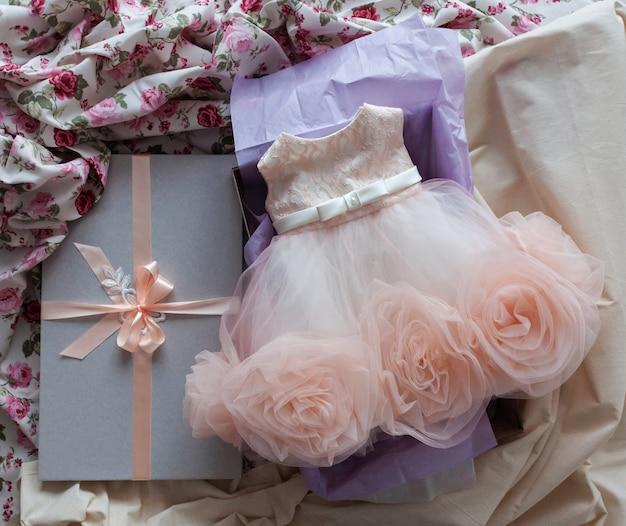 Rosa pastellkleid für kleines mädchen ist in der box verpackt. kleidung in einer box.