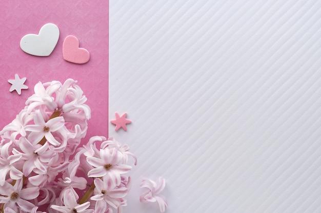 Rosa perlenhyazinthe blüht auf farbigem papier mit dekorativen herzen, kopieraum