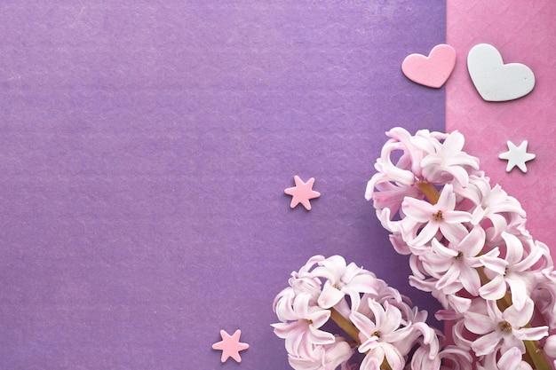 Rosa perlenhyazinthe blüht mit dekorativen herzen auf rosa und purpurrotem farbigem papier, kopieraum