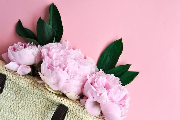 Rosa pfingstrose blüht in sommer gesponnener strohtasche auf rosa.