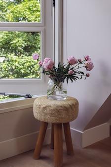 Rosa pfingstrose bouquet in glasvase stehend auf kleinem hocker neben offenem fenster auf grünem hintergrund.