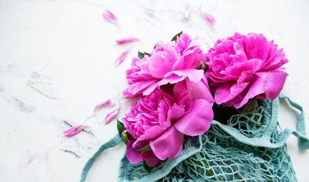 Rosa pfingstrose im stringbeutel auf weißer marmoroberfläche