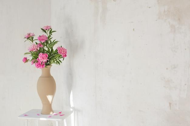 Rosa pfingstrose in keramikvase auf der alten wand des hintergrundes