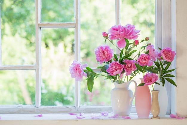 Rosa pfingstrose in vase auf weißem grunge-interieur