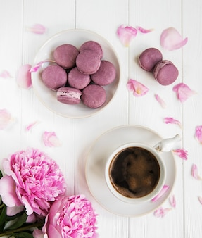 Rosa pfingstrose mit kaffee und macarons